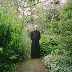 Wooly Rowan Williams with green ferns